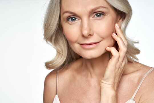 50s mid aged woman touching face skin looking at camera. Attractive mature old woman looking at camera isolated on white background advertising dry skin care treatment anti age skincare. Close up view