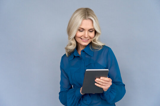 Smiling elegant middle aged older professional business woman leader, consultant manager, looking at device holding digital tablet isolated on grey wall using online technology services on computer.