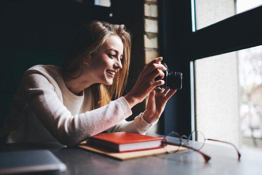 Smiling woman taking photo through window