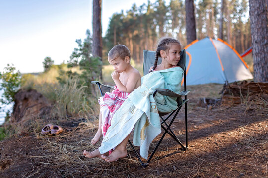 Family local getaway. Kids covering with towels sitting on the camping armchair at campsite and looking at sea wet after swimming, healthy active lifestyle, safe summer, stay location concept