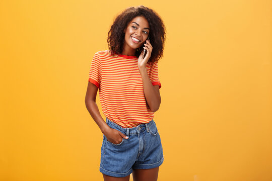 Stylish dark-skinned girl making casual phone call to friend telling all details of after romantic date standing pleased and carefree over orange background in striped t-shirt gazing left with grin