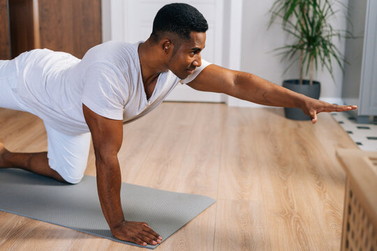 Muscular African-American man working out, doing stretching exercise on yoga mat while watching fitness video online on laptop. Concept of sport training at home gym.