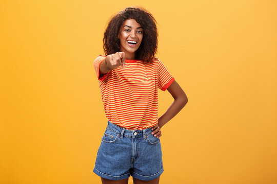 We hire you. Confident happy and awesome dark-skinned fashionable woman with curly hair holding hand on waist pointing at camera with index finger as if picking person or candidate, smiling