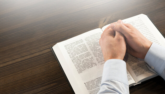 Open Bible book on the table. Prayer. White cup. Young man in shirt prays with folded hands.