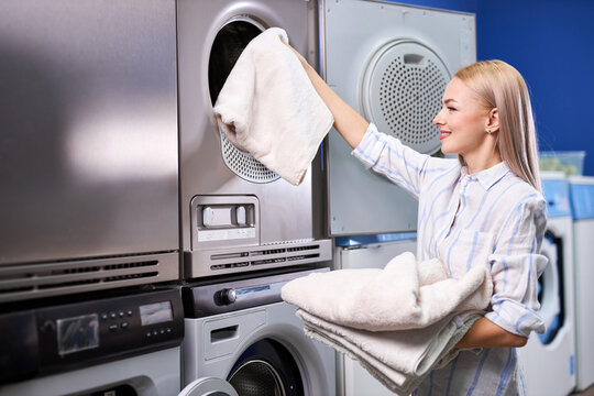 woman standing alone with clean clothes in the self serviced laundry with dryer machines. female in casual wear stands holding basin with clothes, happy after getting clean towels