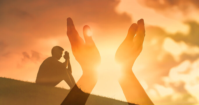 Young man praying reaching out to the sunset sky feeling warm rays of sunshine.
