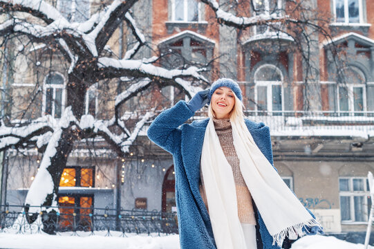 Winter, Christmas, New Year holidays, travel concept: happy smiling woman posing at street of European city. Snowfall. Model wearing blue faux fur coat,  hat, white scarf. Copy, empty space for text