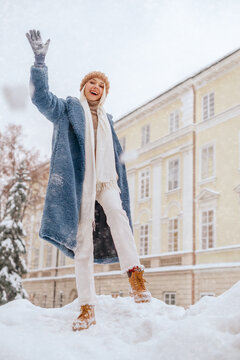 Happy smiling girl playing snowball at street of European city. Snowfall. Model wearing blue faux fur coat, white scarf, hat. Winter, Christmas, New Year holidays, travel conception. Copy space