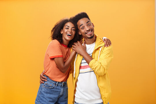 Friends always cover each other. Stylish and carefree loving african american girlfriend hugging boyfriend and smiling broadly touching guy palm hanging around and spending time great together