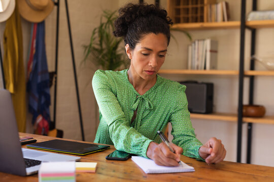 Caucasian woman sitting at desk working from home, writing