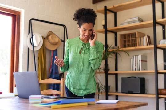 Caucasian woman talking on smartphone, working from home