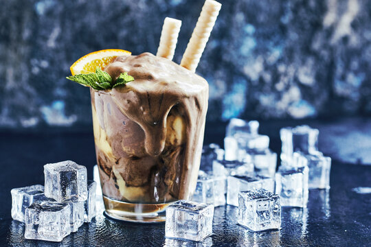 Orange Soda Creamsicle Ice Cream Float in glass decorated with piece of orange, straws and leaves on mint, surrounded by ice cubes on stone table backdrop