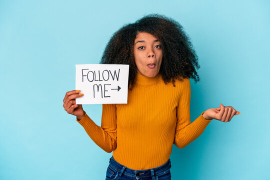Young african american curly woman holding a follow me placard shrugs shoulders and open eyes confused.