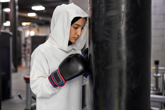 boxing athlete muslim woman in white hijab or islamic sport wear standing by punching bag, arabic fit female is going to fight, stands with serious face. indoor at gym