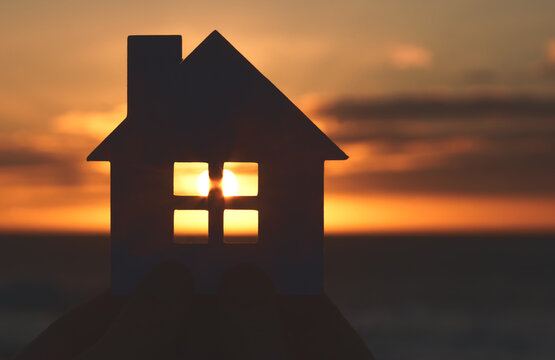 paper house with sunset sun at the beach