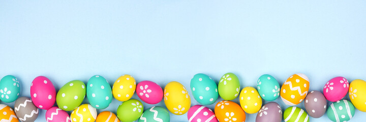 Colorful Easter Egg bottom border over a pastel blue paper banner background. Copy space.