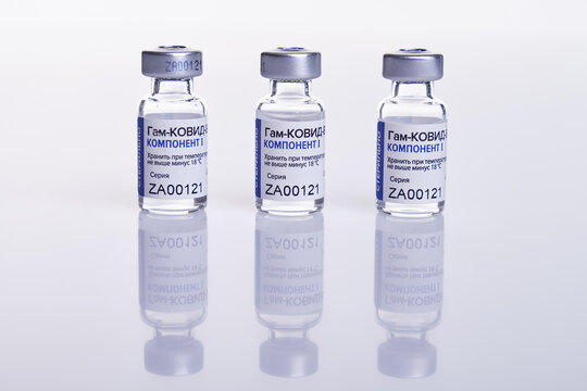 Vaccine vials with Sputnik V vaccine Gam-COVID-Vac on white table with reflection.