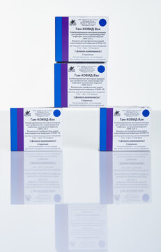 Pyramid of vaccine boxes with Sputnik V vaccine Gam-COVID-Vac on white table with reflection.