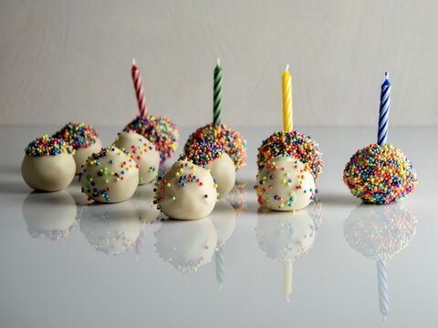 Sprinkle covered white birthday cake balls, truffle dessert, multi colored sprinkle balls with birthday candles sticking up and all the cake balls reflecting in the high gloss white surface.