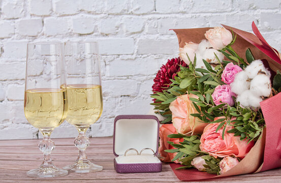 bunch of flowers and wedding rings on white bricks background