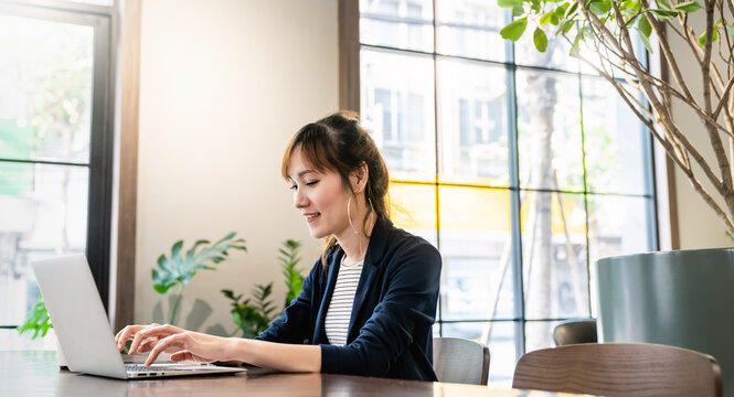 Portrait of smiling beautiful business asian woman in suit working in office desk virtual computer. Small business people employee freelance online sme marketing e-commerce telemarketing concept