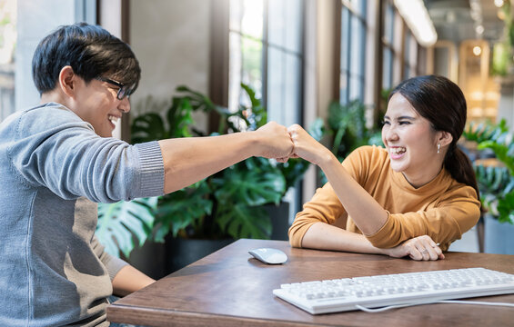 Creative freelance team meeting fist bumps , hands together, asian people teamwork acquisition, brainstorm business people concept. Startup sme friends creative people sale project