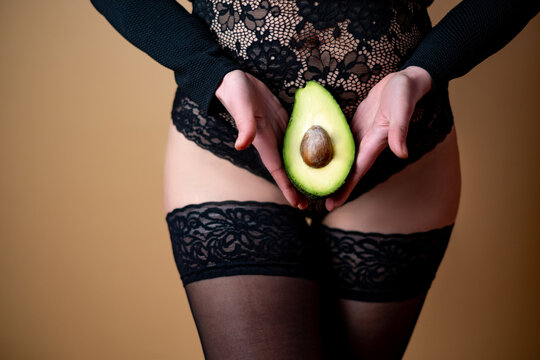 A young girl in beautiful underwear holds half an avocado on the background of her belly. Pregnancy concept