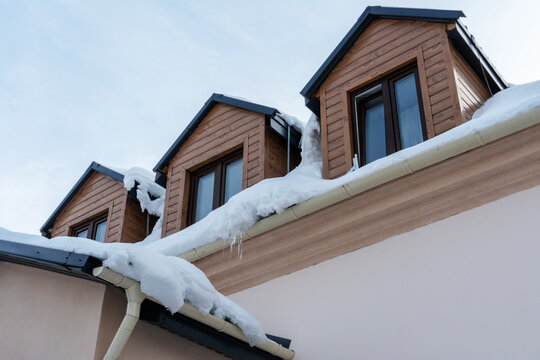 The roofs of the buildings are covered with snow and ice after a big snowfall. Huge icicles hang from the facades of buildings. The fall of icicles carries a danger to people's lives.