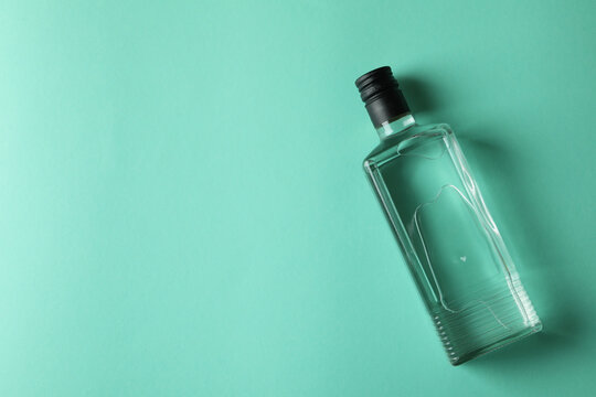 Blank bottle of vodka on mint background, space for text