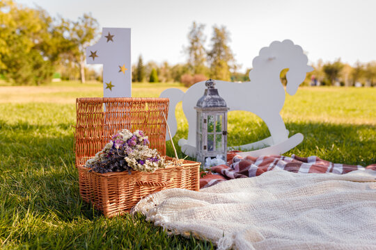 Decorative photozone for 1 year old boy birthday outdoors. Plaid, lantern, number one, basket with dry flowers, rocking horse on green lawn.