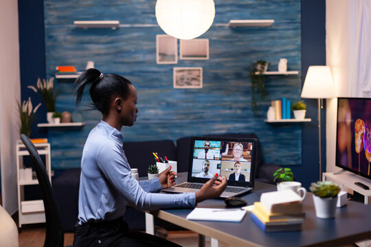 Dark skinned business woman doing remote work speaking with coworkers during video call. Using modern technology network wireless talking on virtual meeting doing overtime.