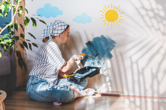 young girl paints the wall of the house with a roller in blue. Gender equality, stereotypes, March 8. Hobby, work as a house painter. Comfort, spring renewal, home decor.Selective focus