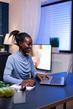 Dark skinned freelancer in the course of webinar smiling while taking notes sitting at desk late at night. Black entrepreneur sitting in personal workplace writing on keyboard.