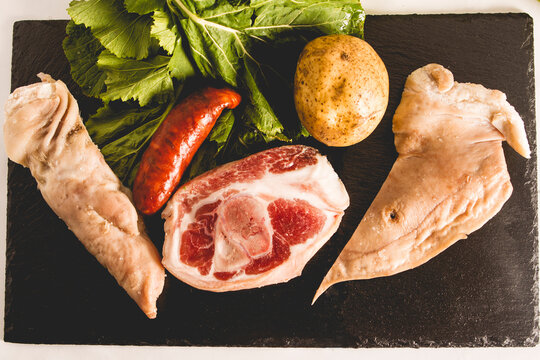 ingredients of the Galician stew recipe during carnivals consisting of potato, pork leg, lacon, smoked ear, chorizo ​​and turnip green