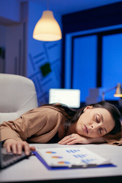 Portrait of overworked businesswoman sleeping desk in corporate office. Employee falling asleep while working late at night alone in the office for important company project.