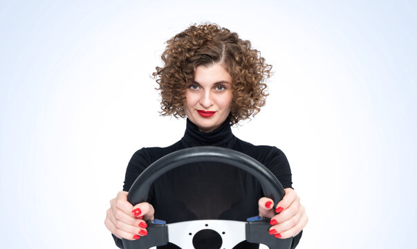 Confident young beautiful smiling girl driving a car, front view on light blue background