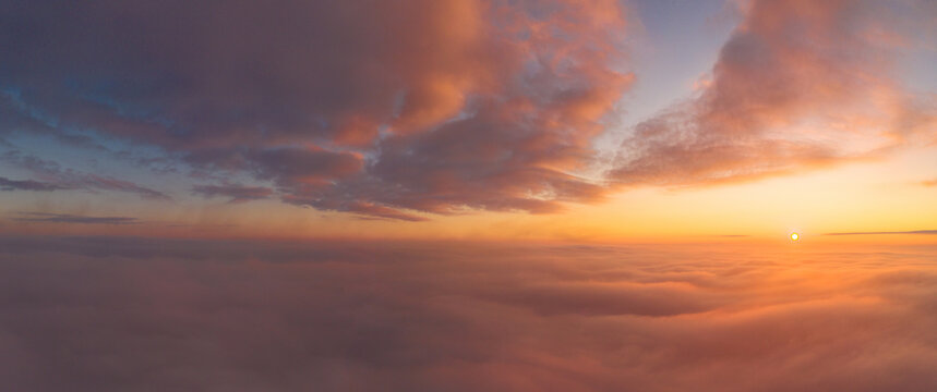 panoramic view from an airplane on a beautiful saturated sunrise above the clouds in red and orange shades