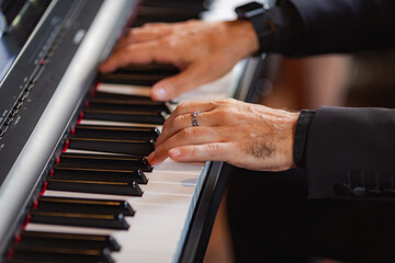 Hands of a man playing the piano.
