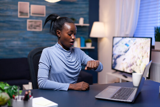 African business woman checking time looking at wrist watch working late on deadline from home office. Nervous black manager doing overtime working on computer.