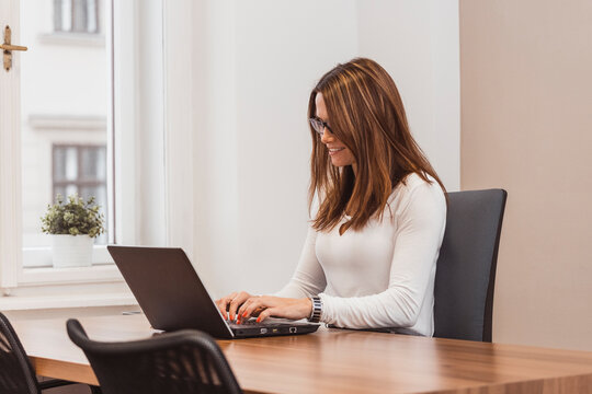 Smiling business woman typing on laptop, side view. Succesful people