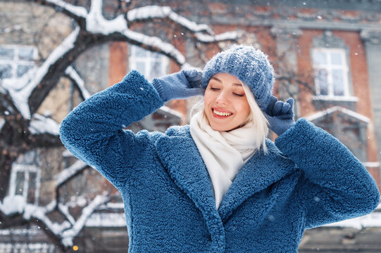 Winter, Christmas, New Year holidays, travel concept: happy smiling woman posing at street of European city. Snowfall. Model wearing blue faux fur coat, knitted beanie hat. Copy, empty space for text