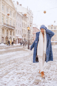 Happy smiling fashionable woman walking at street of European city. Snowfall. Model wearing blue faux fur coat, white scarf, hat. Winter, Christmas, New Year holidays, travel conception. Copy space