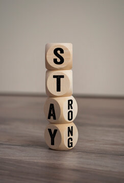Tower made of cubes, dice or blocks showing the words stay strong on wooden background