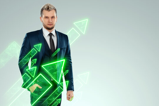 A businessman in a business suit looking for an opportunity against the background of green arrows pointing up. Development concept, start-up, investment search. Copy space.