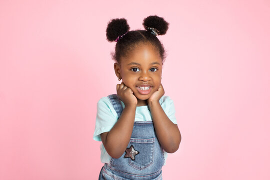 Funny happy smiling little cute African-american girl, with afro hair in two ponytails, posing with her arms under face and looking at camera over pink background. Close up studio shot
