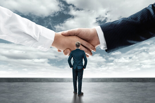 A businessman in a business suit looks at the big handshake. Creative background. The concept of cooperation, an important contract, the conclusion of a flea contract, a merger.