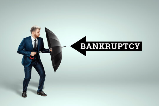 A man in a business suit stands with an umbrella in his hands and is defending himself from bankruptcy. Savings and assets protection, insurance concept.