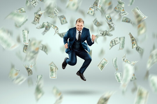 A man in a business suit jumps for joy against the background of falling dollars, rain of money. Business concept, bookmaker, sports betting, investment, passive income.