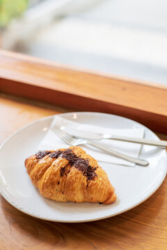 French chocolate croissant on plate on wooden table and nature sunlight with shadow through from window.
