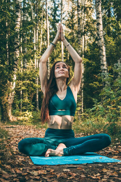 The woman practices yoga outdoors. She sits on the grass looking at her folded palms up. Hatha yoga. Asana in yoga. Surya Namaskar or Salutation to the Sun yoga poses.